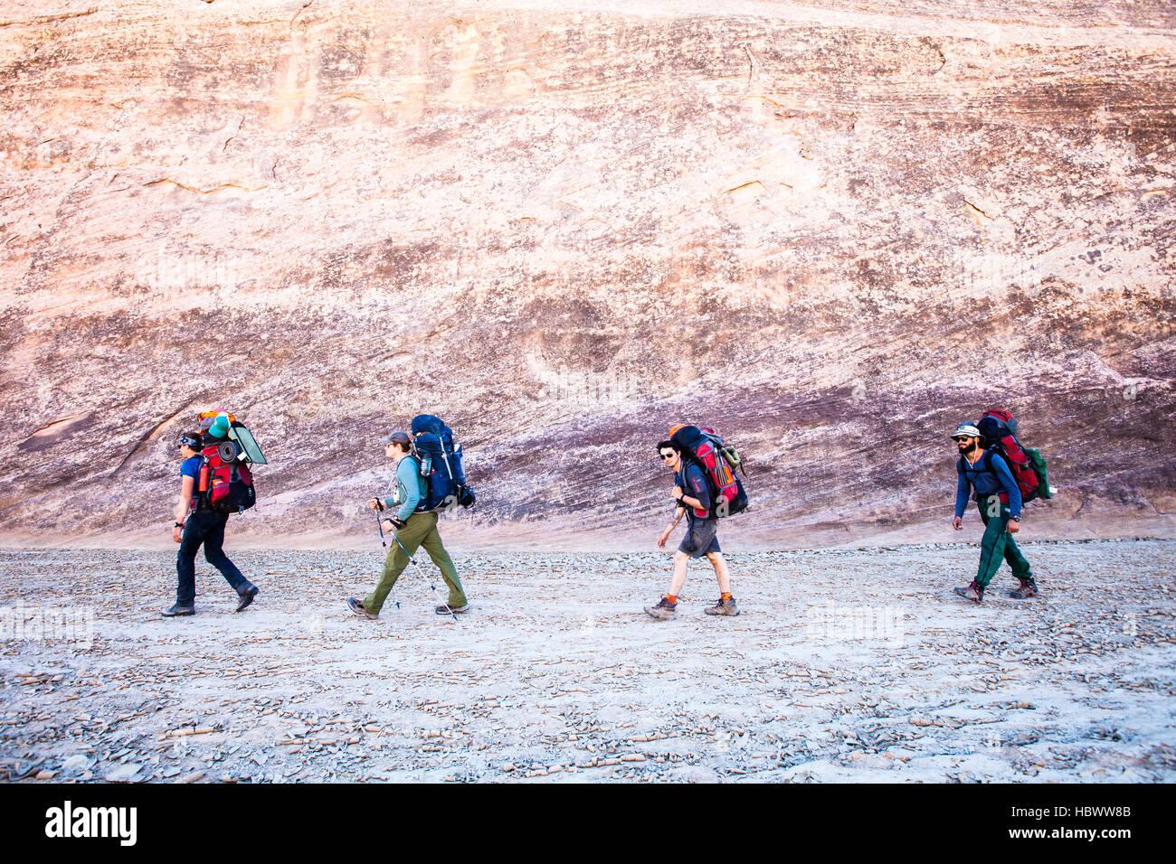 Un gruppo di giovani con lo zaino in spalla attraverso un lavaggio a secco nei canyon dello Utah Immagini Stock