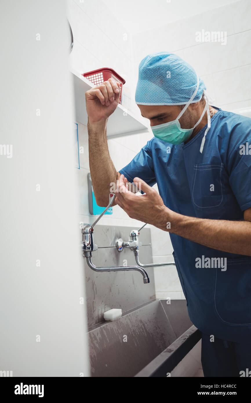 Chirurgo maschio lavarsi le mani prima di funzionamento utilizzando la tecnica corretta per la pulizia Immagini Stock