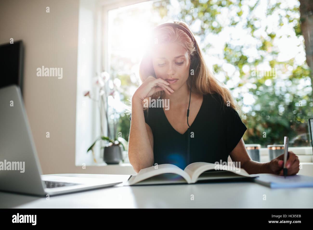 Giovane donna seduta a tavola con laptop e prendendo appunti nel libro. Studentessa studiare a casa. Foto Stock