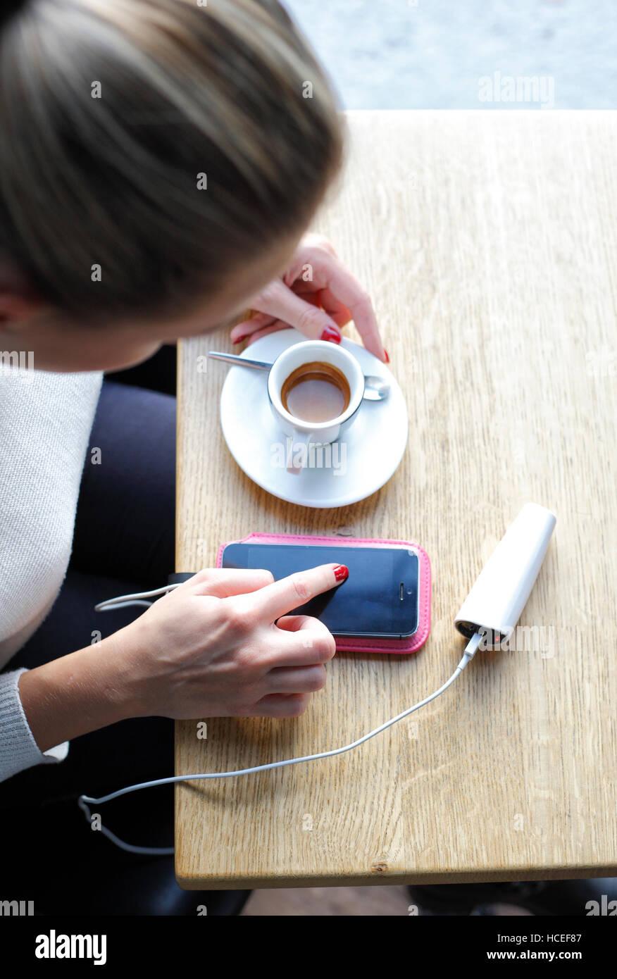 Caricamento del telefono cellulare e digitando nel caffè bar Immagini Stock