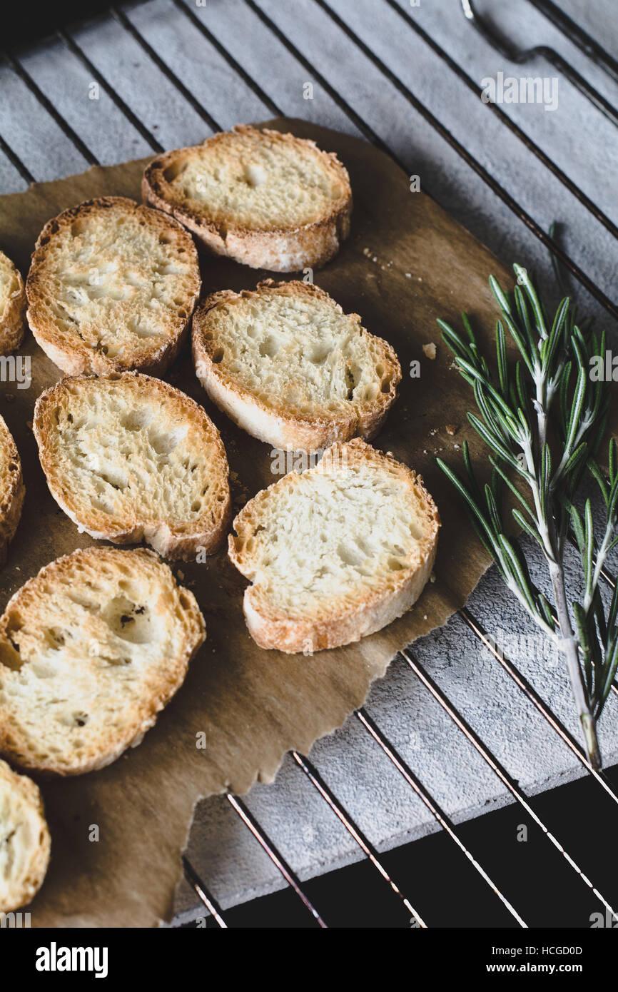 Tostare il pane baguette su carta pergamena sul raffreddamento per rack Foto Stock