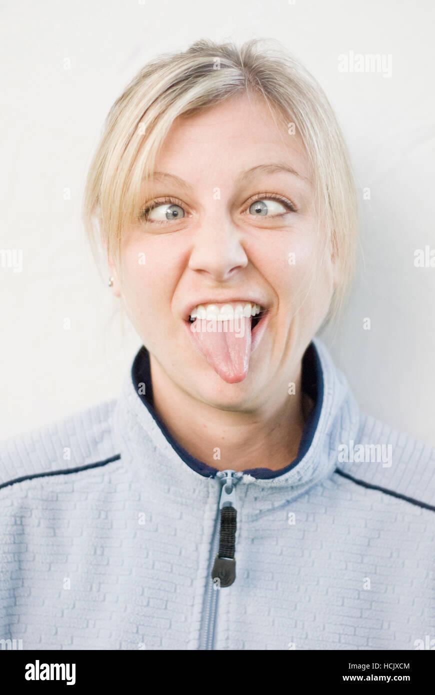 Ironico ritratto di una giovane donna che fa una faccia buffa con gli occhi incrociati e sporgenti dalla sua lingua. Immagini Stock