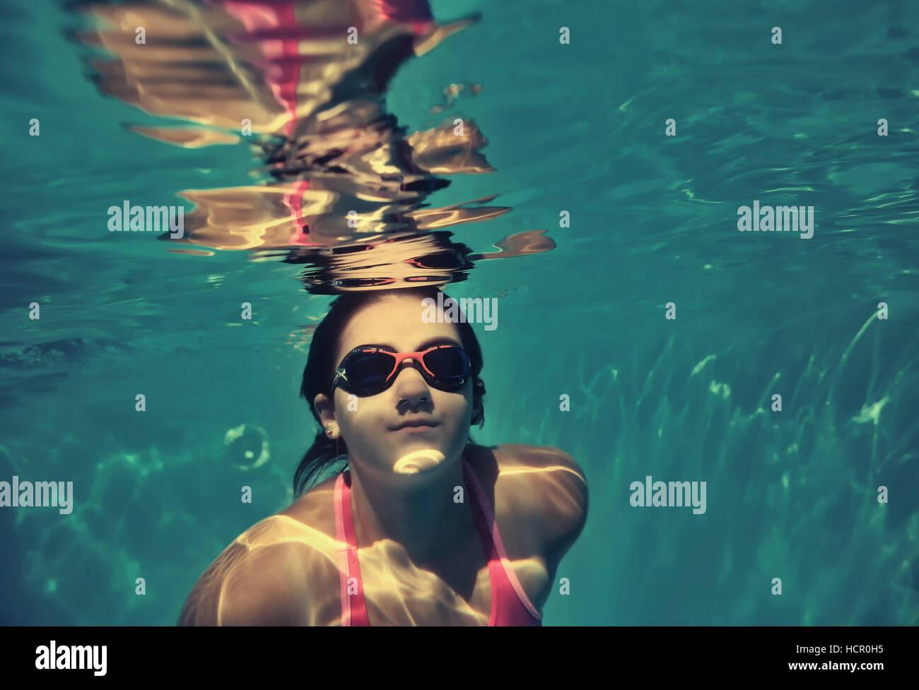 Ragazza di nuoto sott'acqua in piscina. Immagini Stock