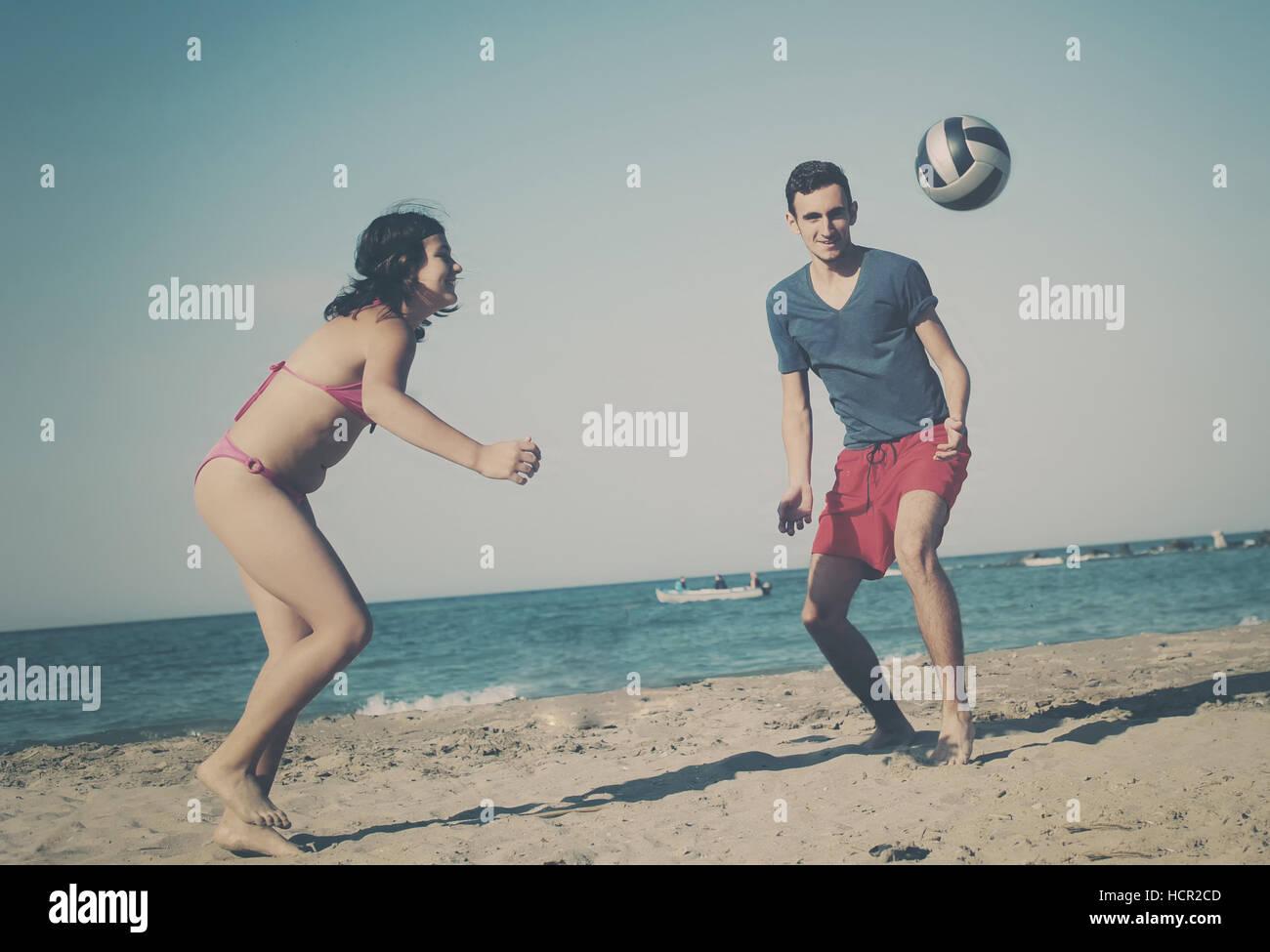 Giovane giocando a pallavolo sulla spiaggia Immagini Stock