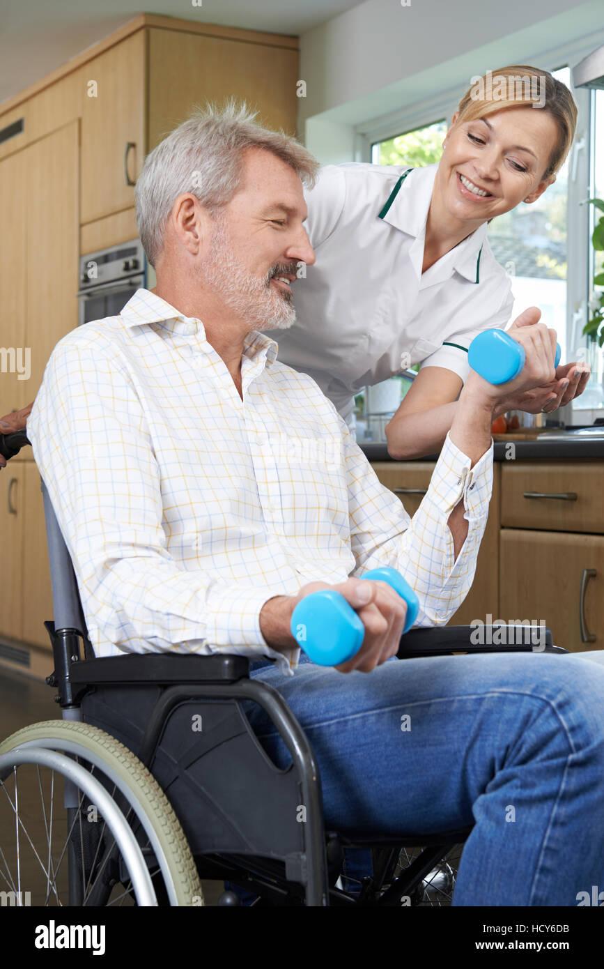 Fisioterapista aiutare l uomo in sedia a rotelle con gli esercizi Immagini Stock