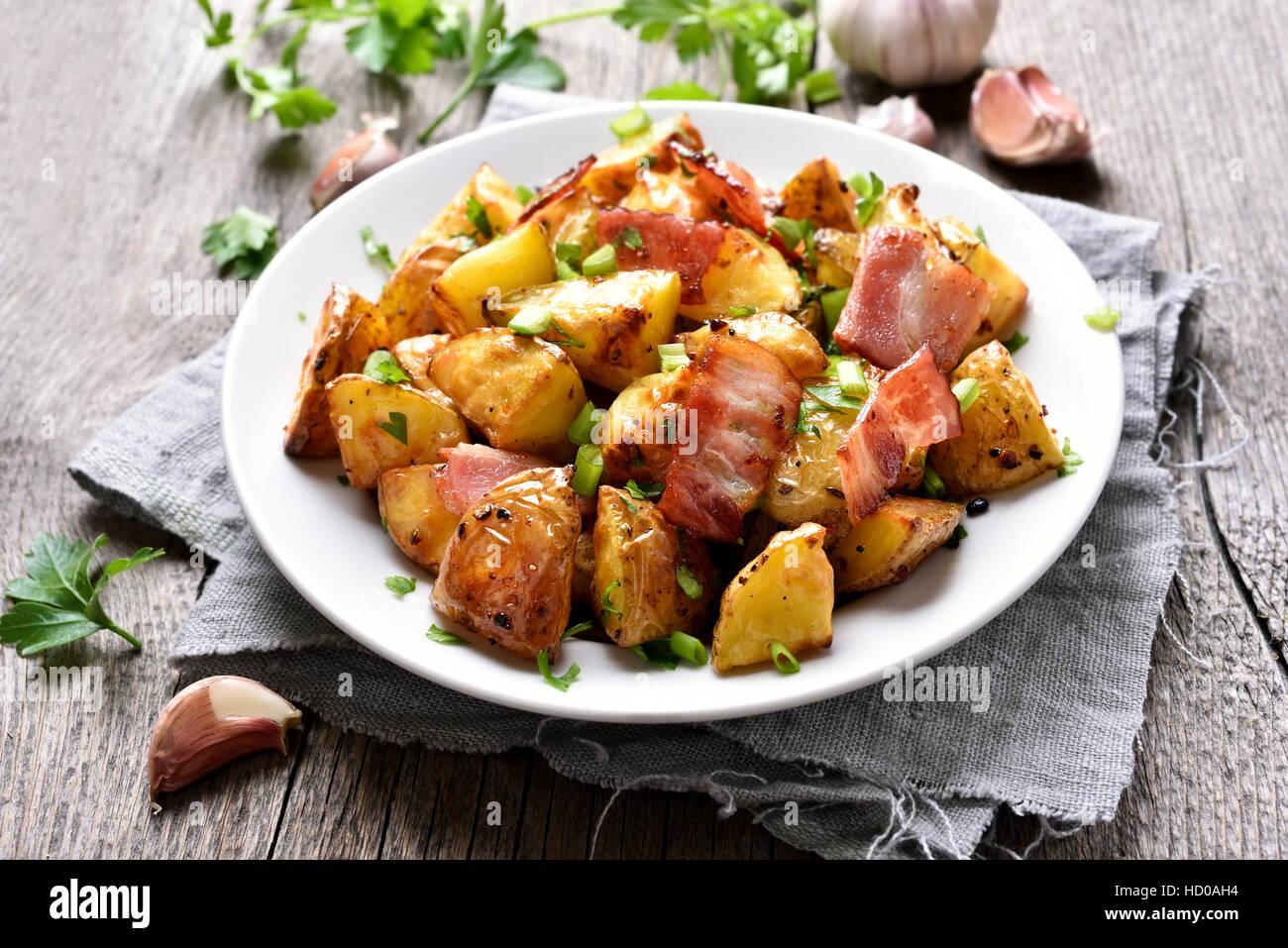 Patate arrosto con pancetta e cipolla verde sulla piastra Immagini Stock
