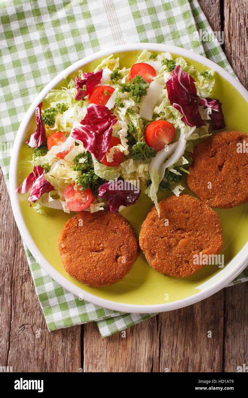 Dietetici hamburger di carote e insalata fresca mix close-up su una piastra. vista verticale da sopra Immagini Stock