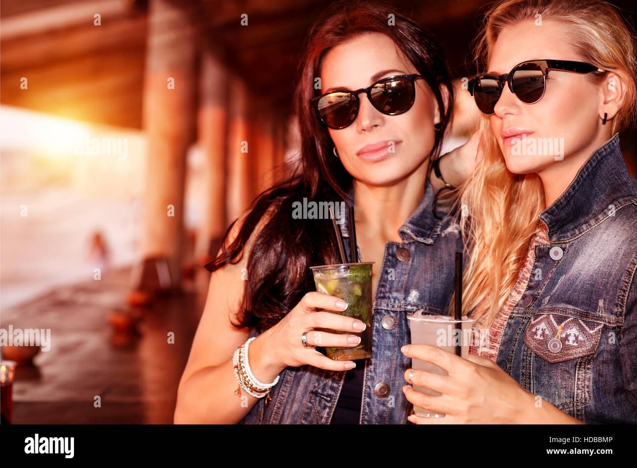 Due donne bellissime con bevande rinfrescanti per divertirsi in spiaggia Cafe, elegante da indossare occhiali da Immagini Stock