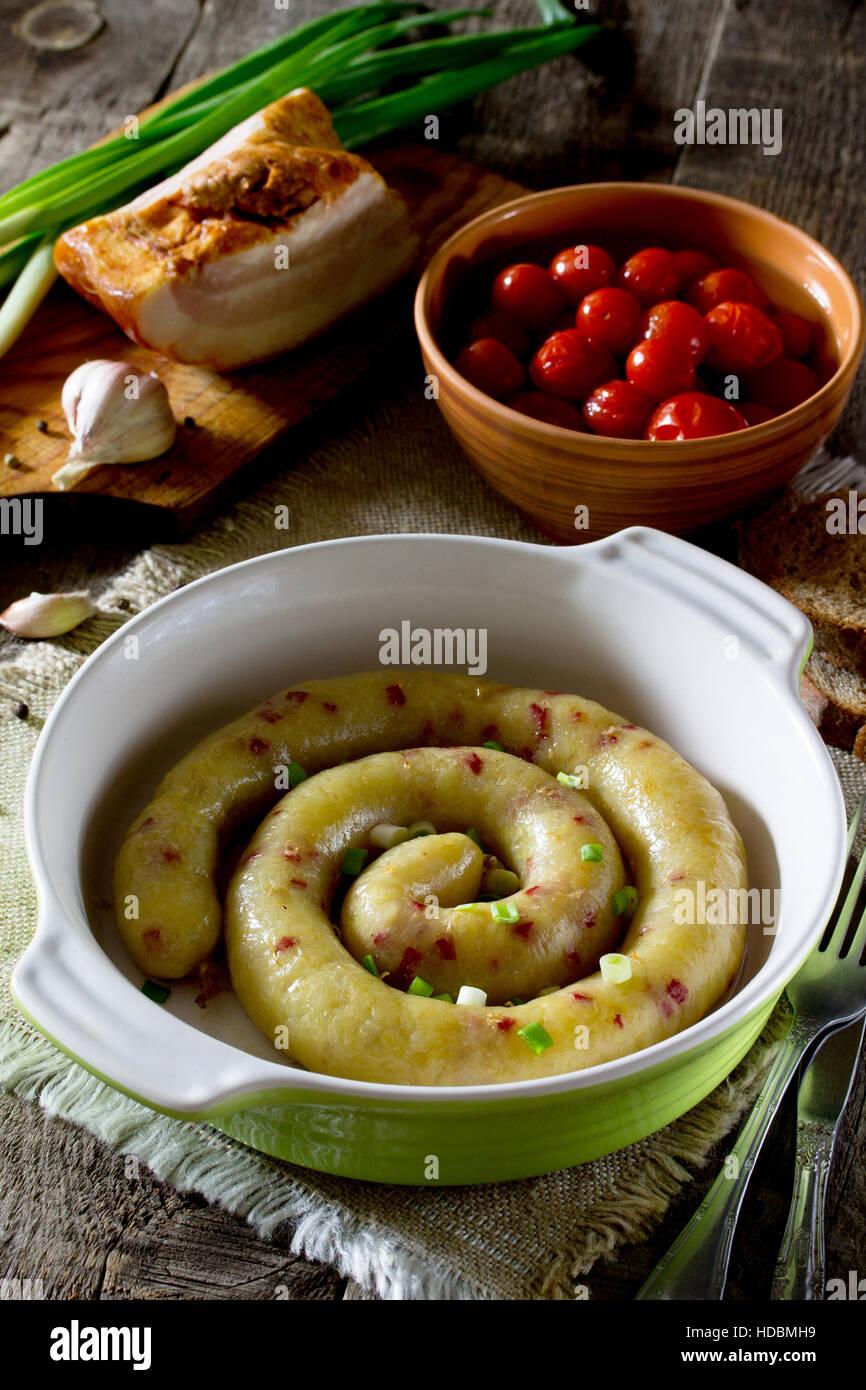 In casa la salsiccia al forno con patate e pancetta su un sfondo rustico. Immagini Stock