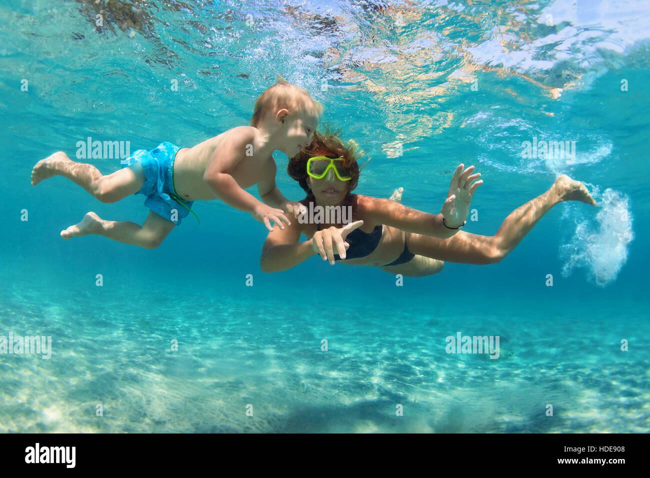 La famiglia felice. Madre con bambino figlio subacquea immersioni in mare piscina. Uno stile di vita sano e attivo, Immagini Stock