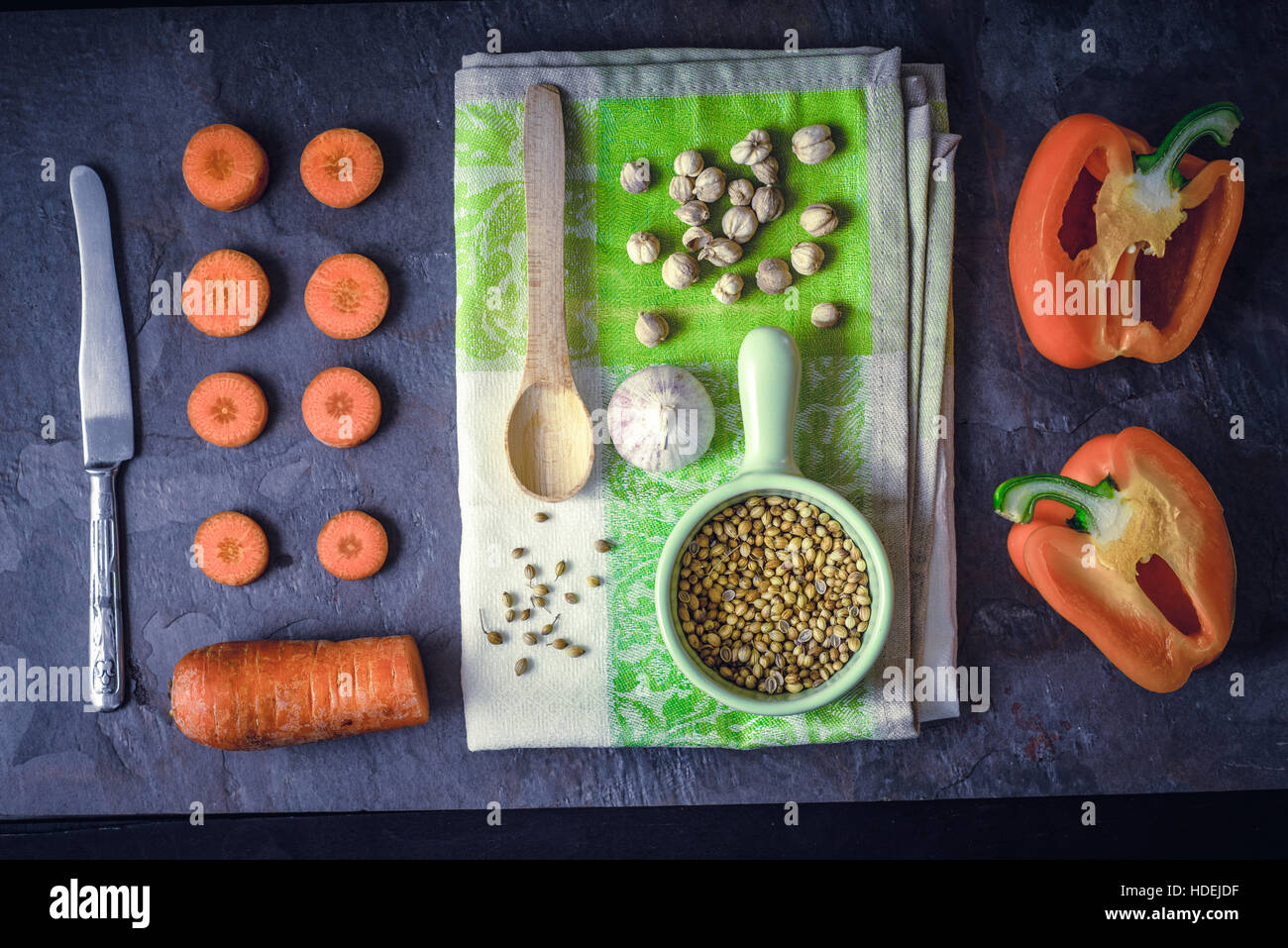 Verdure di colore arancione con il condimento sulla pietra scura sullo sfondo vista superiore Immagini Stock