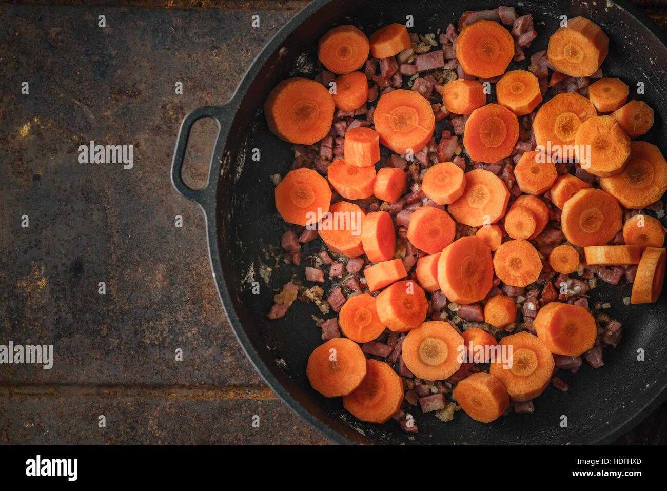 Le carote e la pancetta in padella su sfondo di metallo Immagini Stock