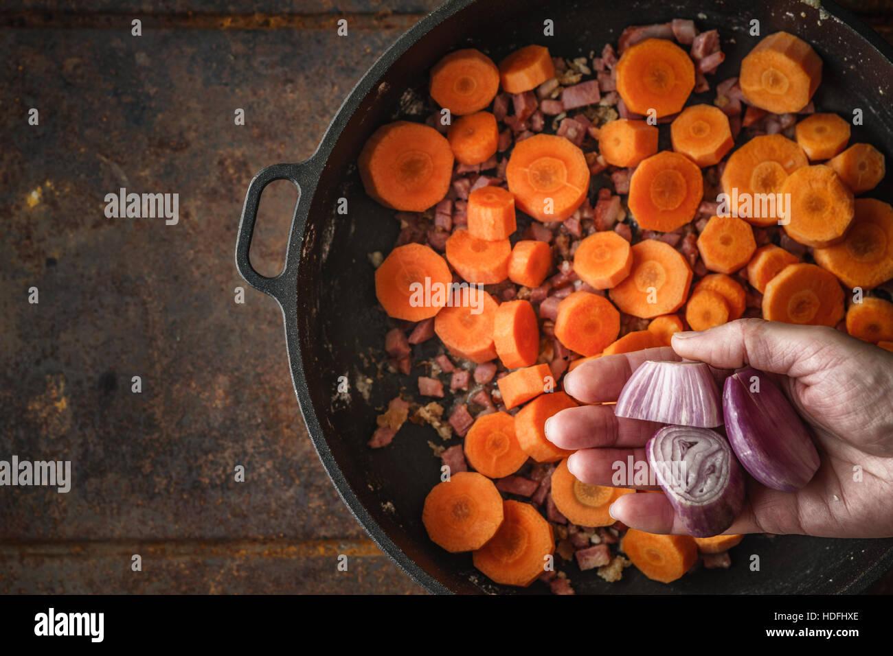 Aggiunta di scalogno in padella con la pancetta e carote vista superiore Immagini Stock