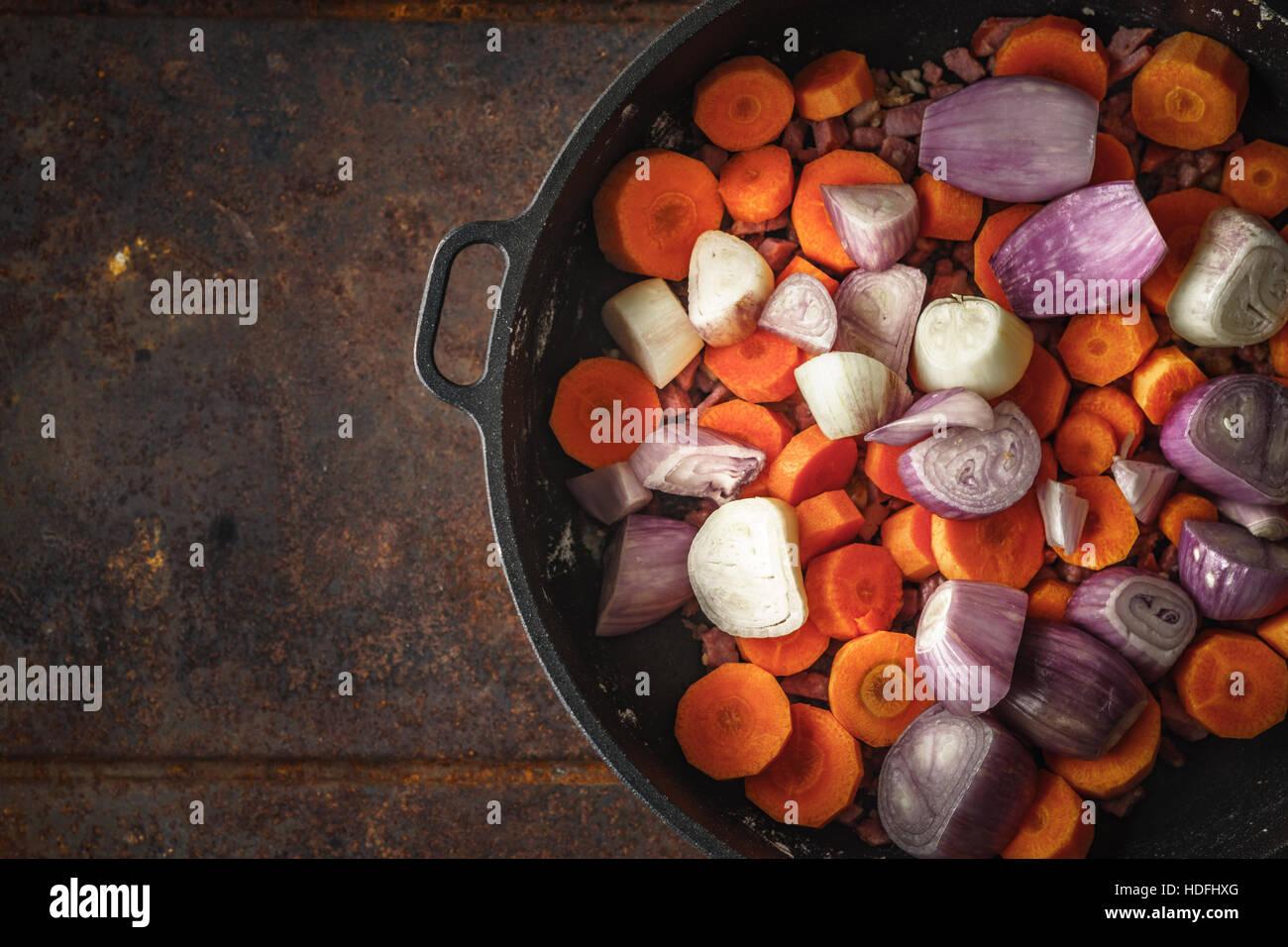 Lo scalogno e le carote in padella su sfondo di metallo Immagini Stock