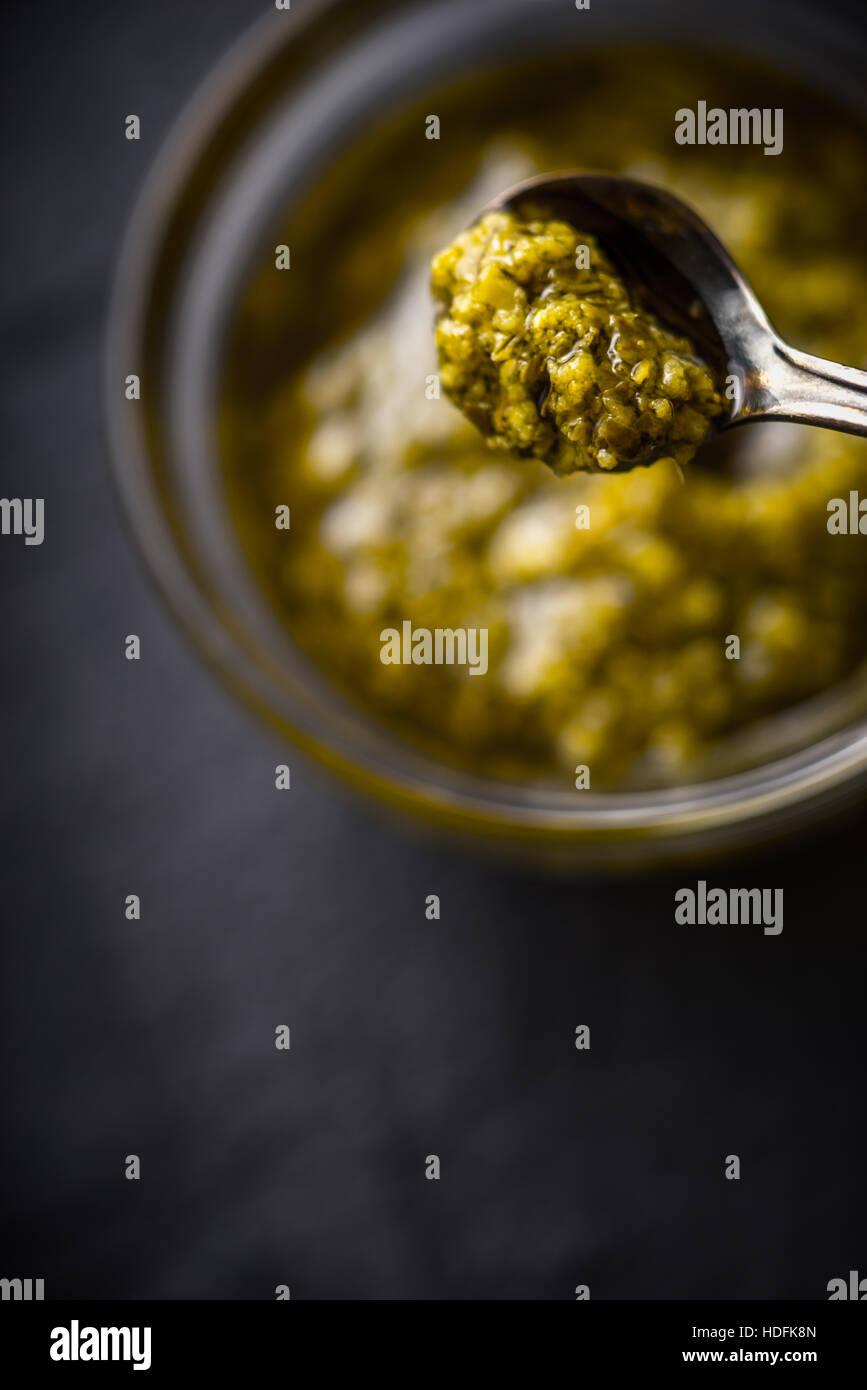 Il Pesto in metallo cucchiaio con sfocate verticale jar Immagini Stock