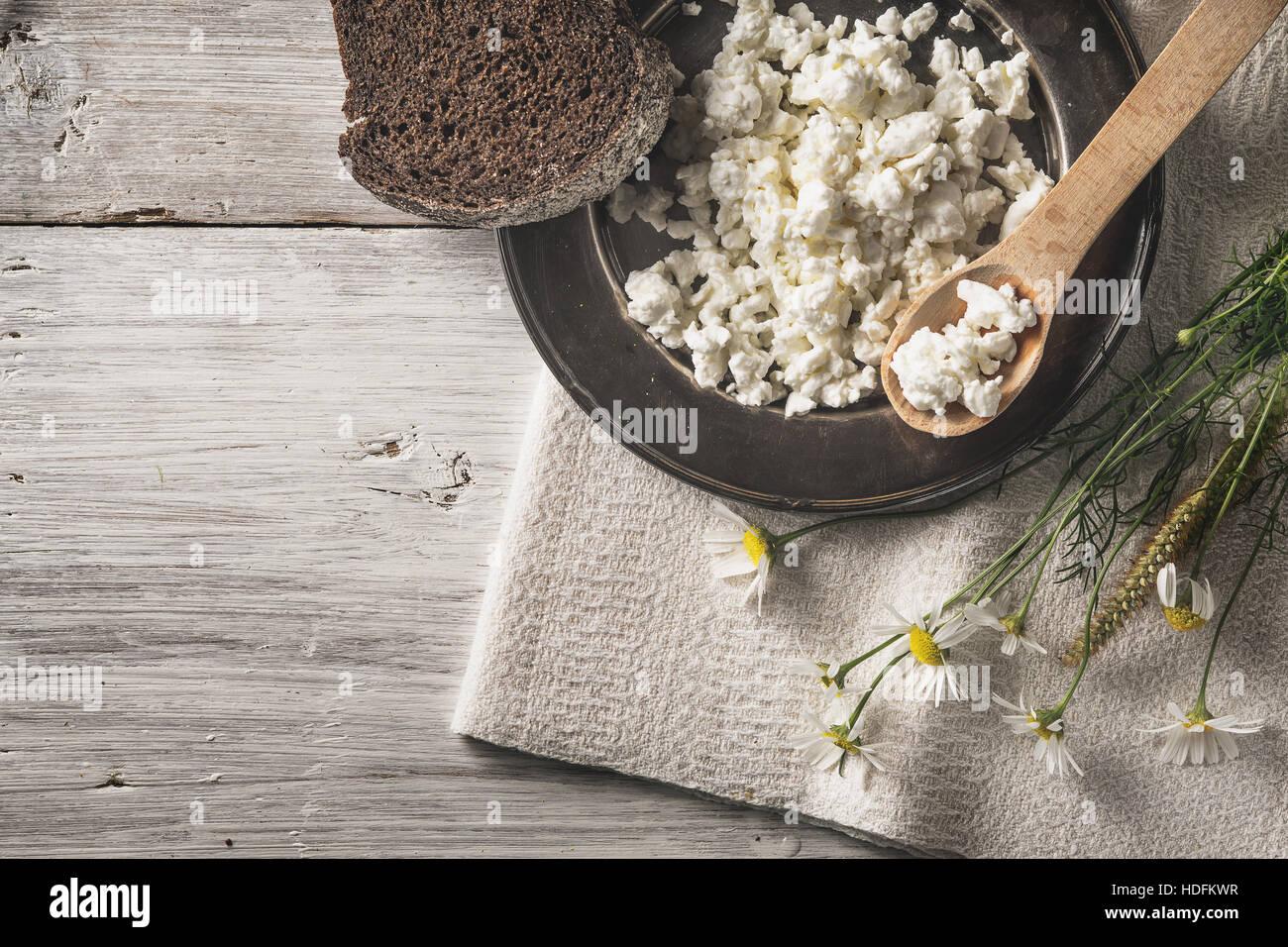 Fresco formaggio cottage con pane e fiori sul bianco tavolo in legno vista superiore Immagini Stock