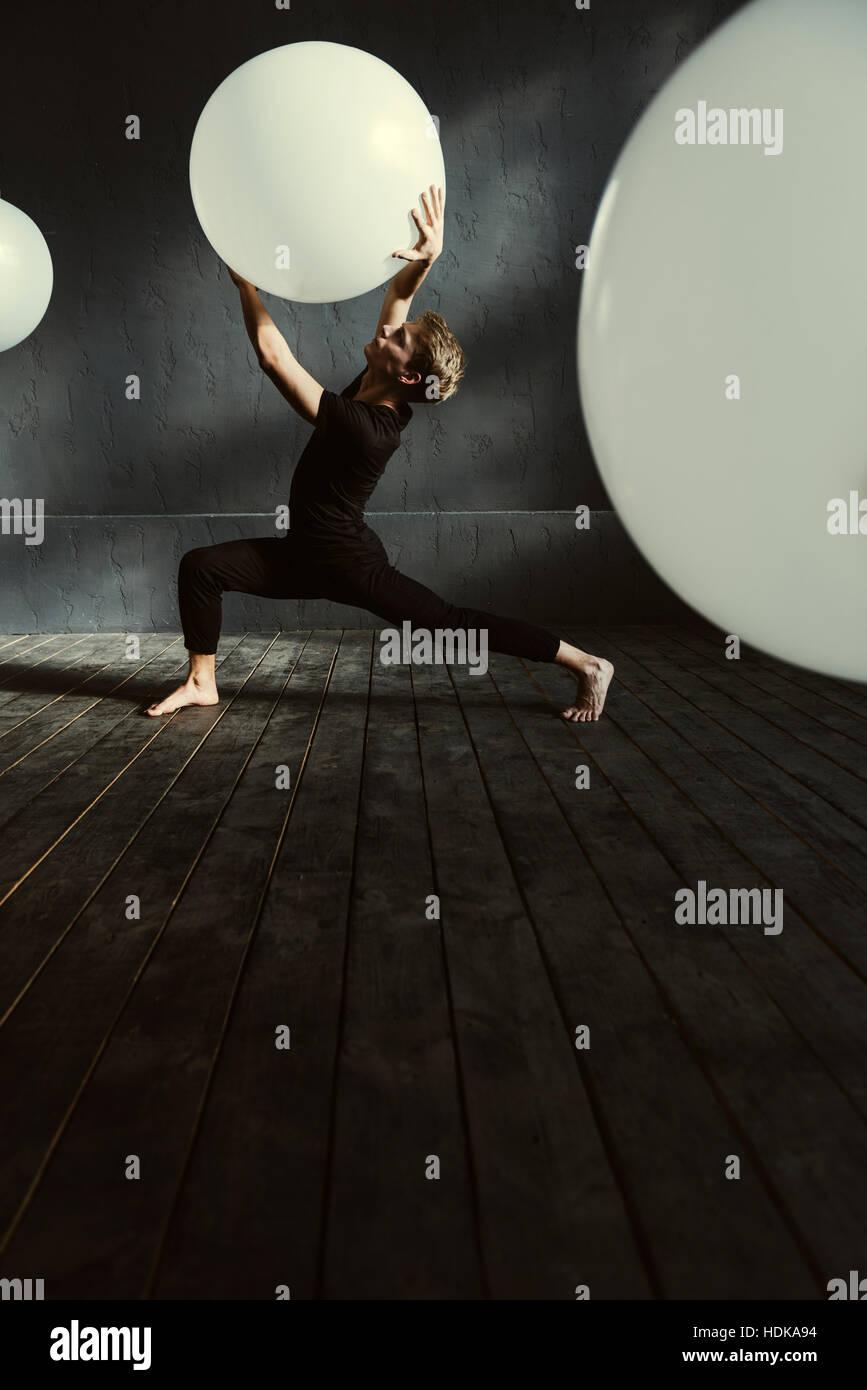 Ballerino magistrale esecuzione nella buia stanza illuminata Immagini Stock