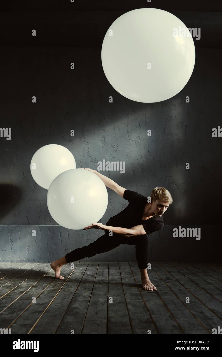 Ballerino potente esecuzione di fronte alla parete scura Immagini Stock