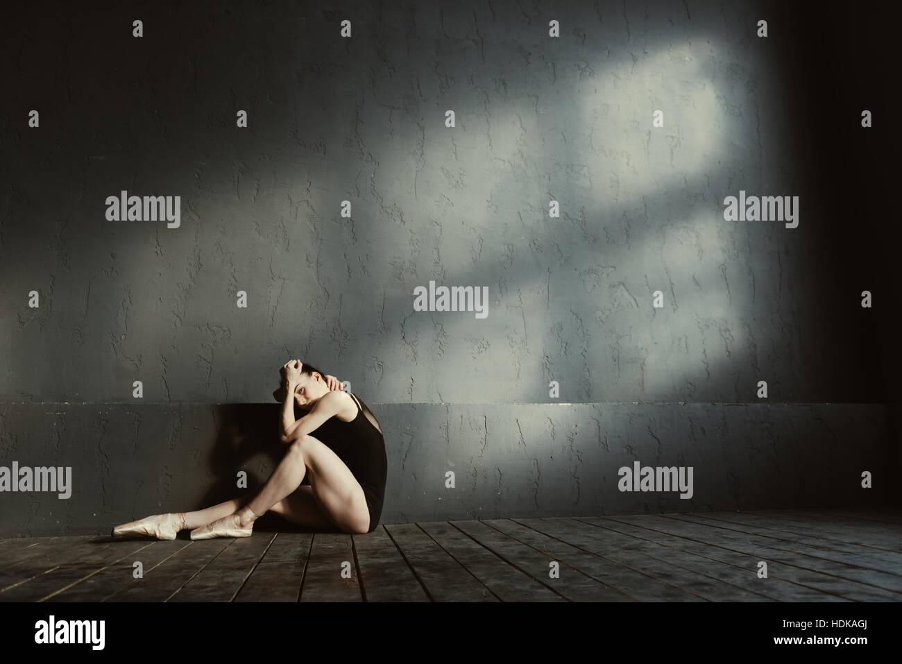 Turbare i giovani seduta ginnasta isolato nel buio stanza illuminata Foto Stock