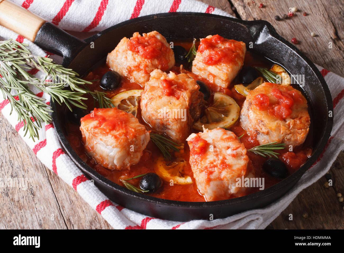 Filetto di pesce in salsa di pomodoro in una padella e gli ingredienti sul tavolo orizzontale. Immagini Stock