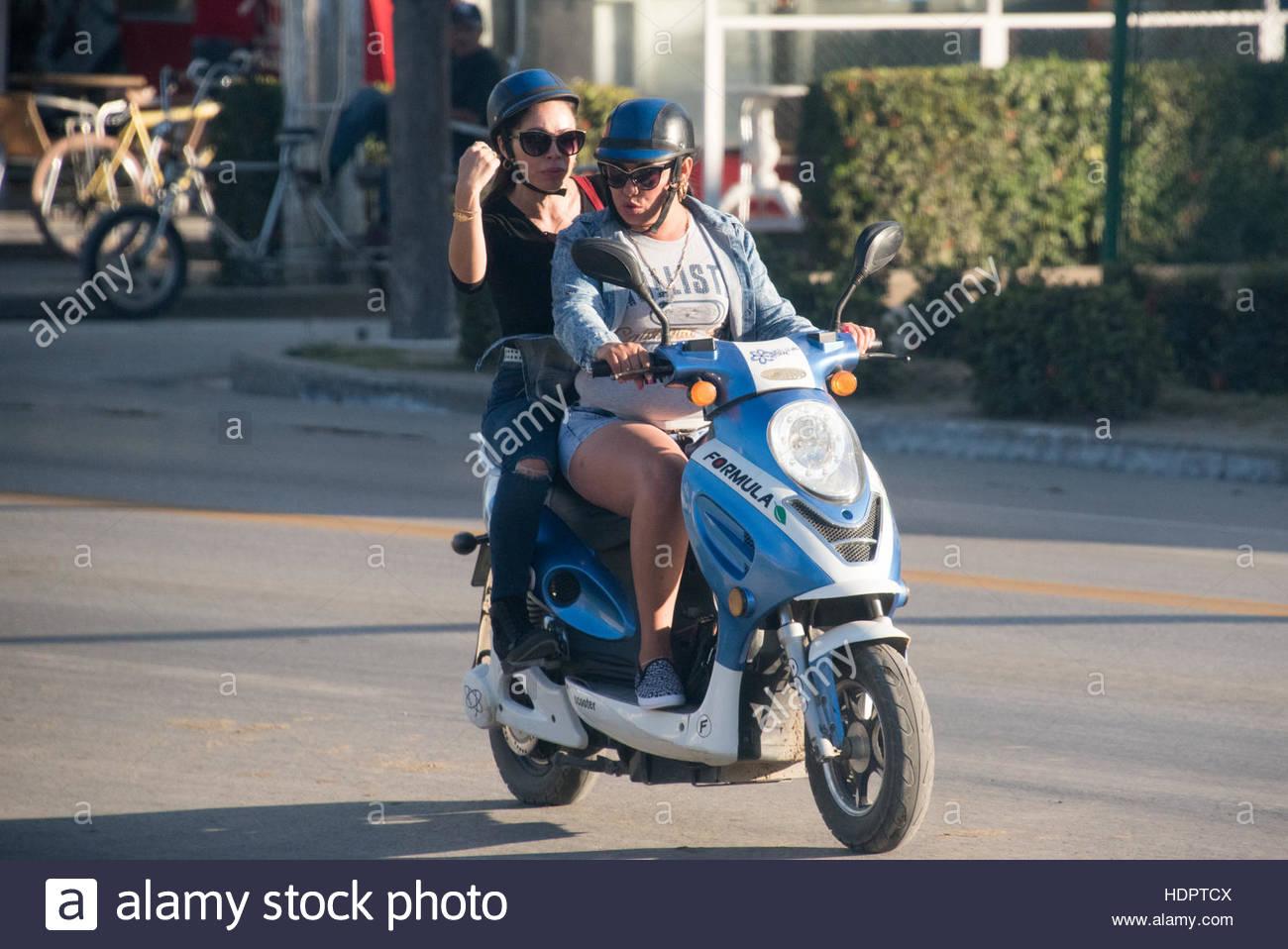 Donne Equitazione un scooter elettrico. Il popolo cubano lo stile di vita di tutti i giorni i dettagli. Immagini Stock
