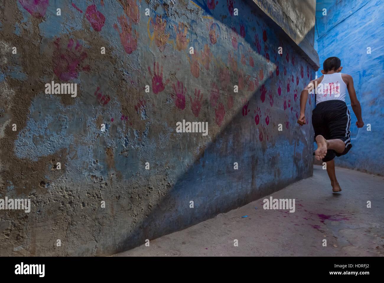 Ragazzo in esecuzione in un vicolo, Jodhpur, Rajasthan, India Immagini Stock