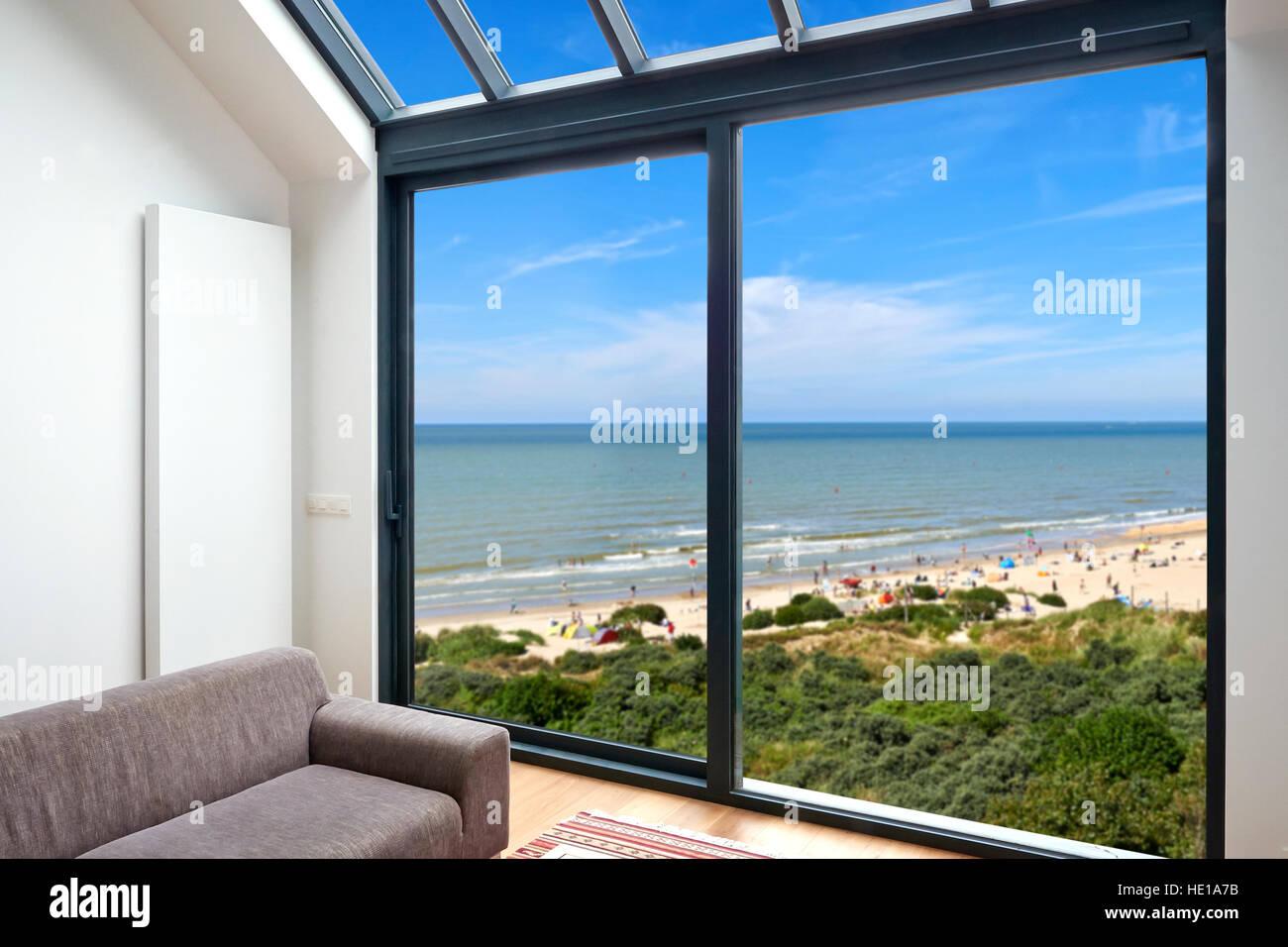 Soggiorno moderno con grandi finestre e vista sul mare Immagini Stock