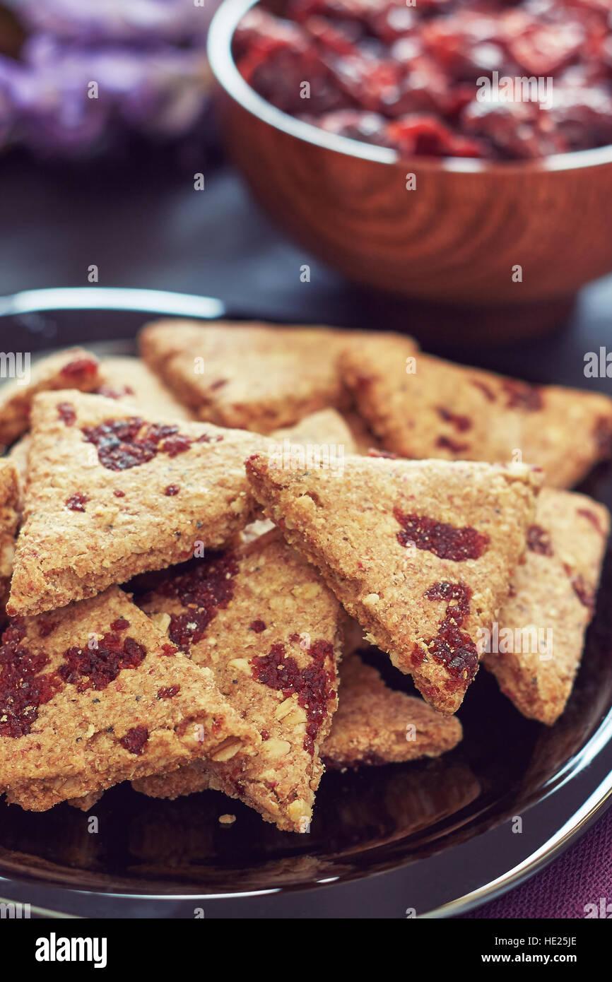 Tutto il grano i cookie con mirtilli rossi secchi su nero lo sfondo di legno Immagini Stock