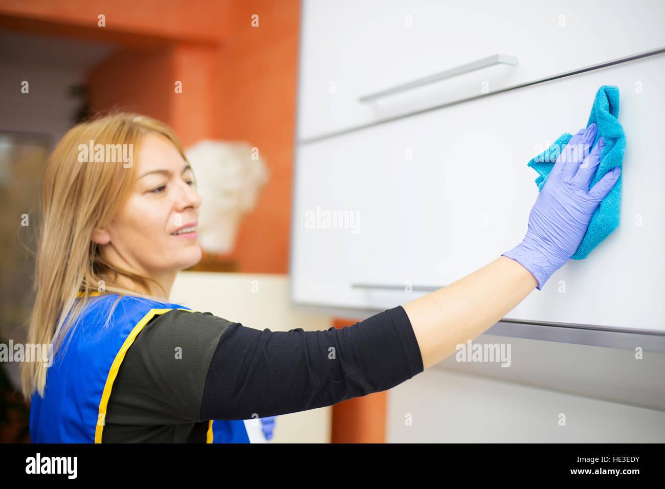 Donna al lavoro professionale di pulizia domestica in studio dentistico Immagini Stock