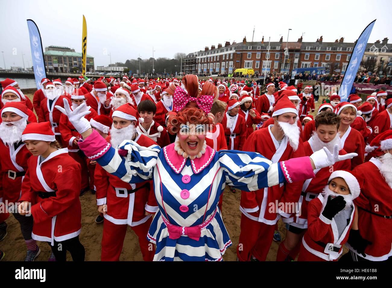 Spiaggia di Weymouth nel Dorset, Regno Unito. Xviii Dicembre, 2016. Inseguire il pudding Santa correre sulla spiaggia Immagini Stock