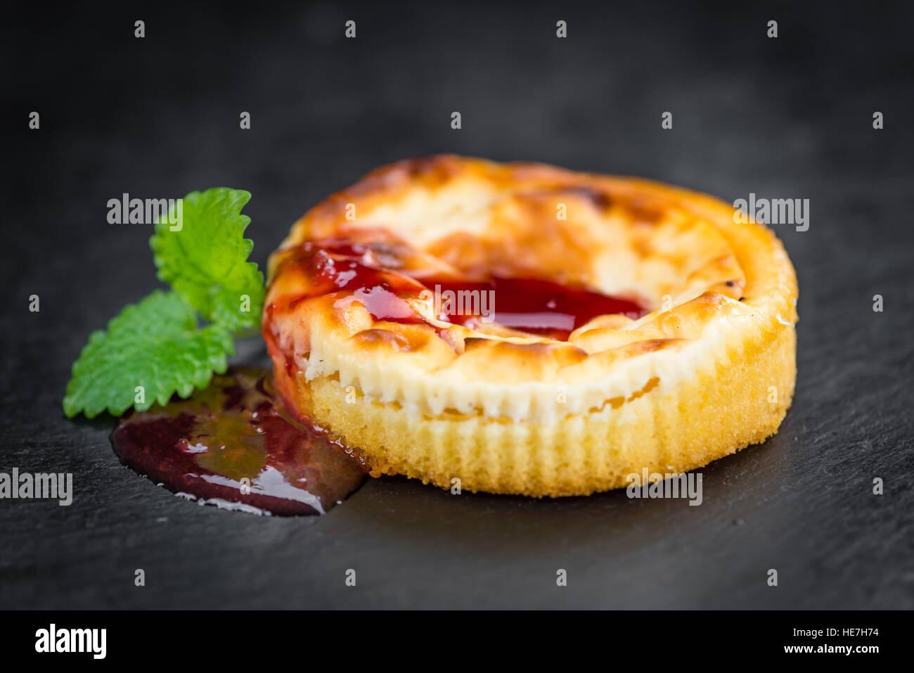 Cheesecake con salsa su un vintage lastra di ardesia (close-up shot; messa a fuoco selettiva) Foto Stock