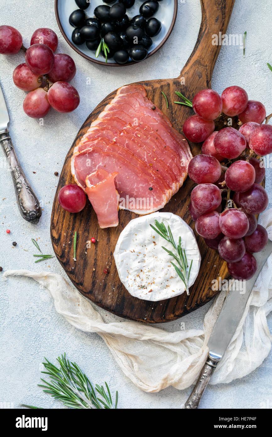 Piastra di antipasti di carne, uva, il formaggio e le olive. Antipasti o il concetto di tapas. Vista superiore Immagini Stock
