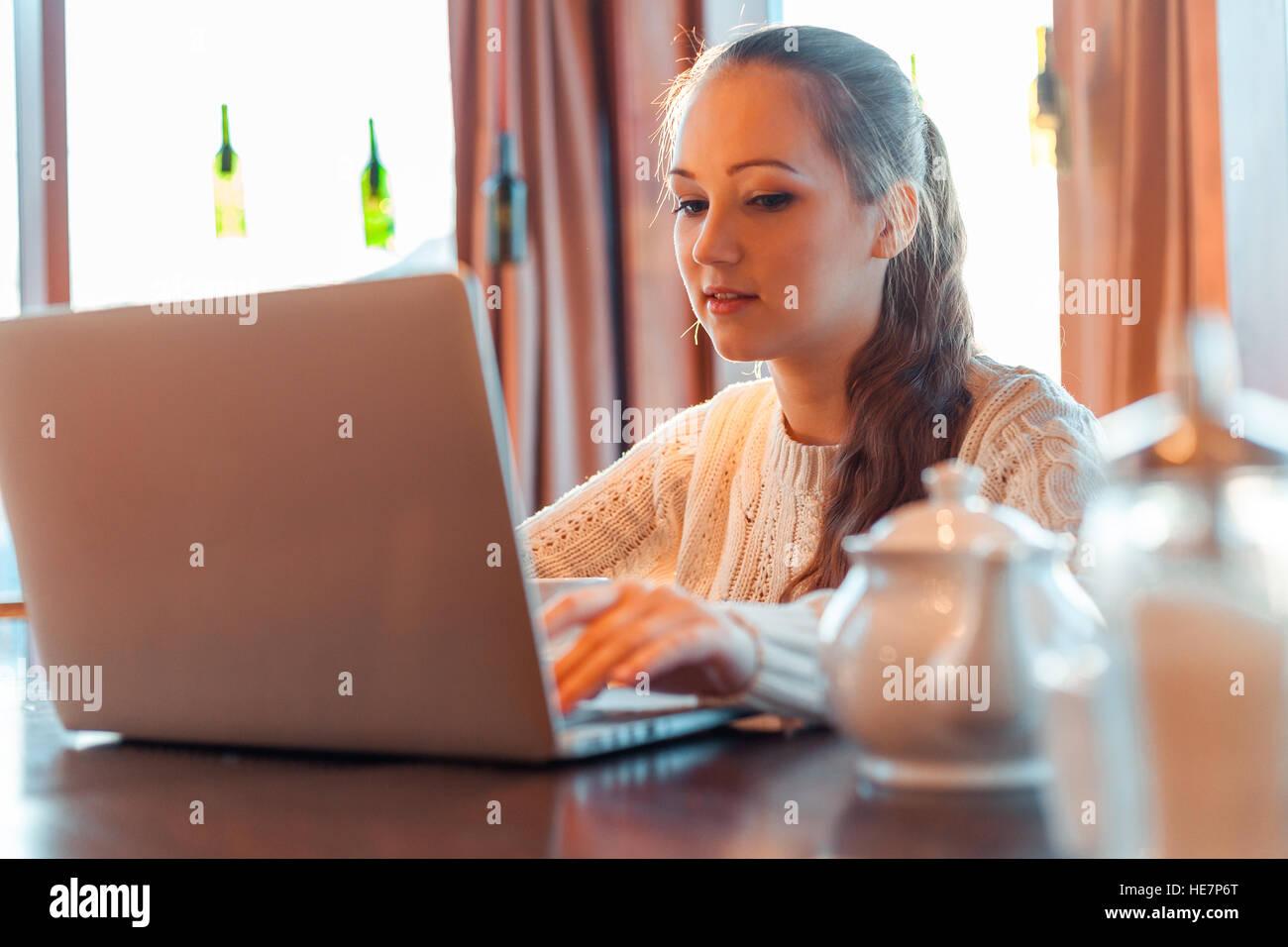 Yong donna un lavoro al computer portatile in cafe Foto Stock