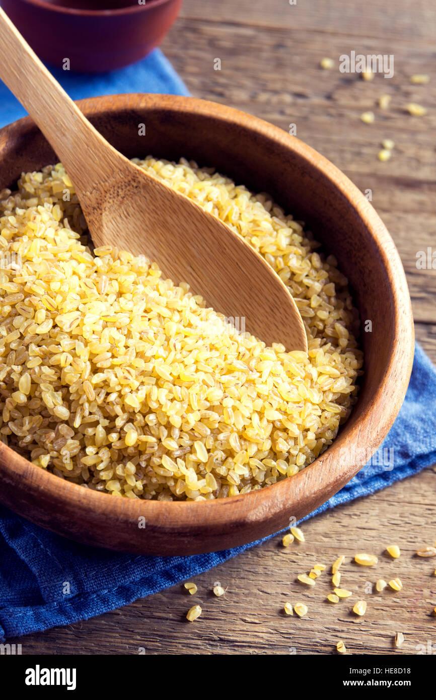 Organici di bulgur, cuscus materie del grano nel recipiente di ceramica close up - cibo sano ingrediente Immagini Stock