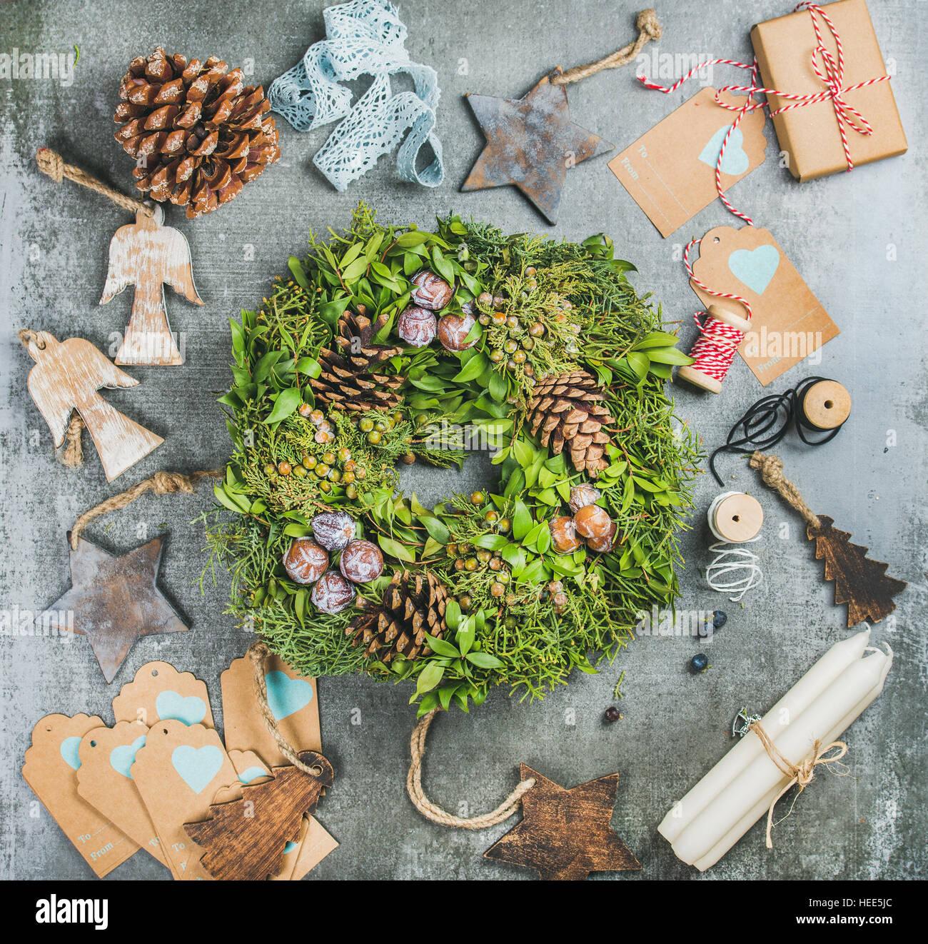 Natale verde corona, pigne, giocattoli di legno, candele, dei materiali decorativi Immagini Stock