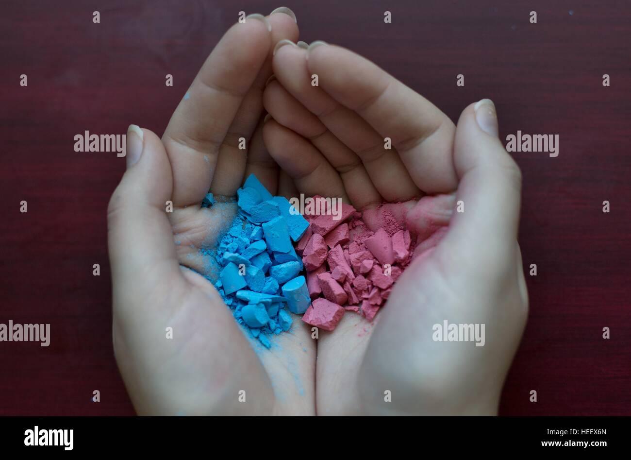 A tazza tenendo le mani rosa e blu gesso sbriciolato. Immagini Stock