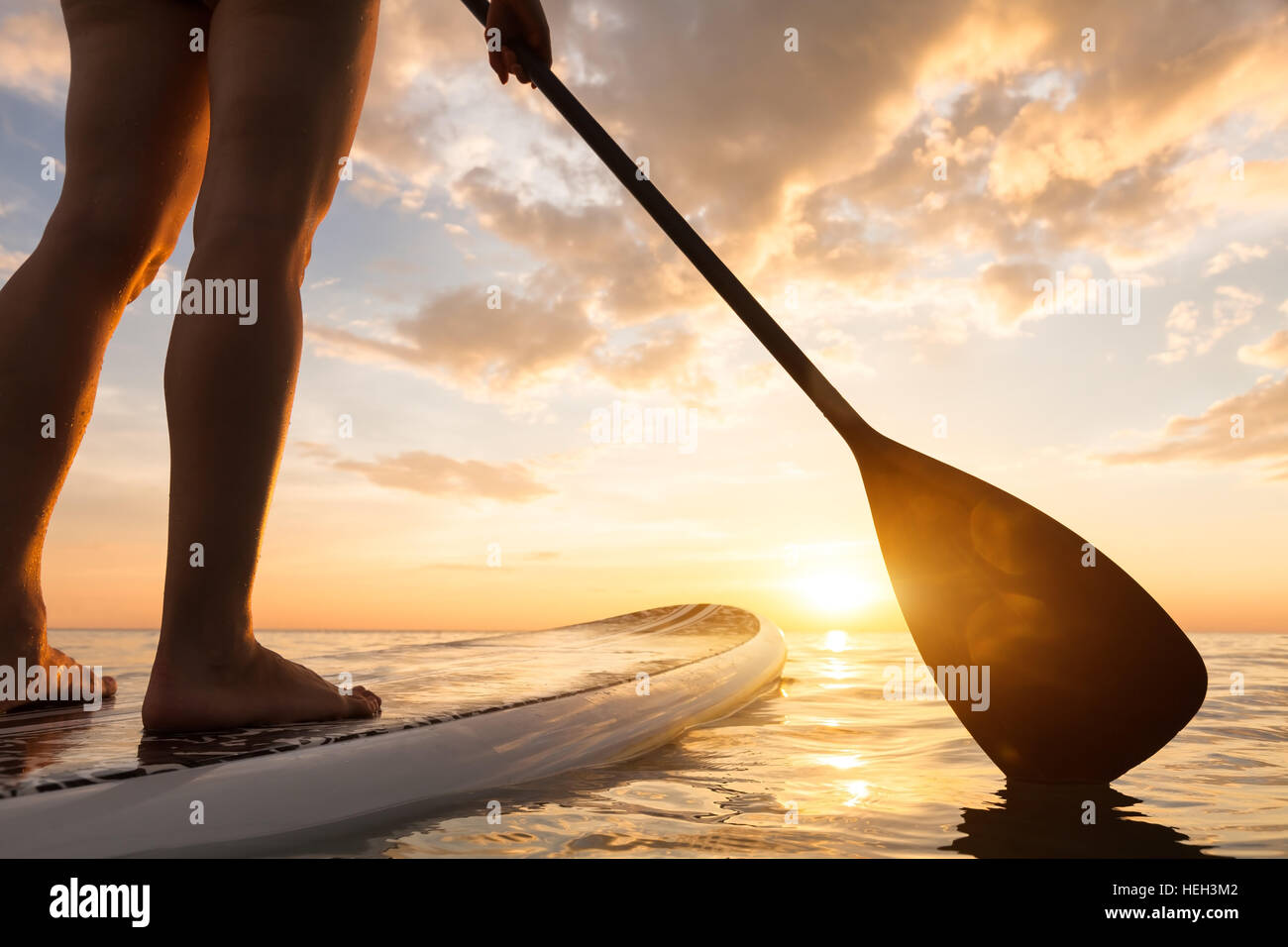 Stand Up Paddle imbarco su un mare tranquillo con una calda estate i colori del tramonto, close-up di gambe Foto Stock