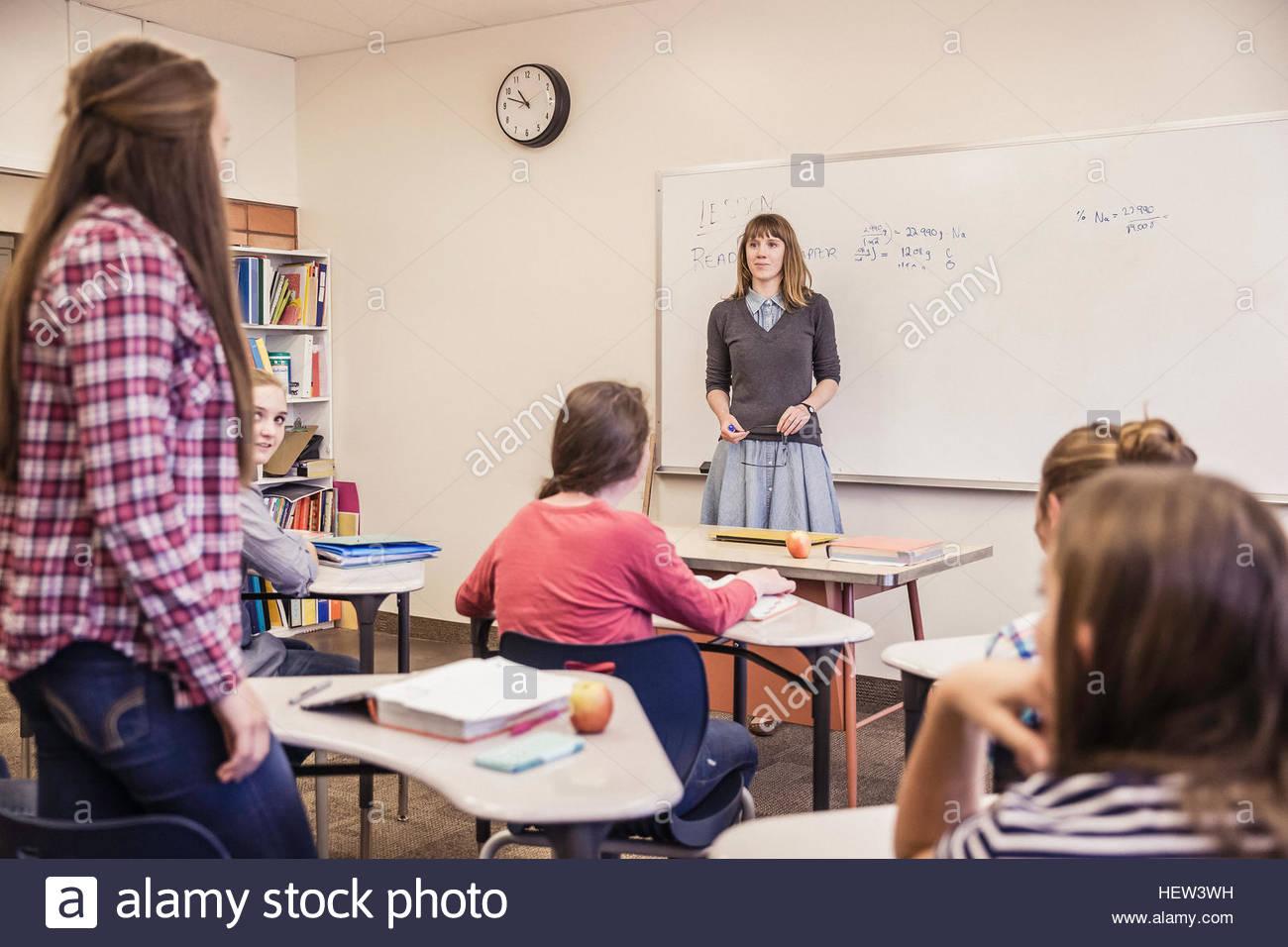 Insegnante femmina interrogatorio ragazza adolescente durante l'alta scuola lezione Immagini Stock