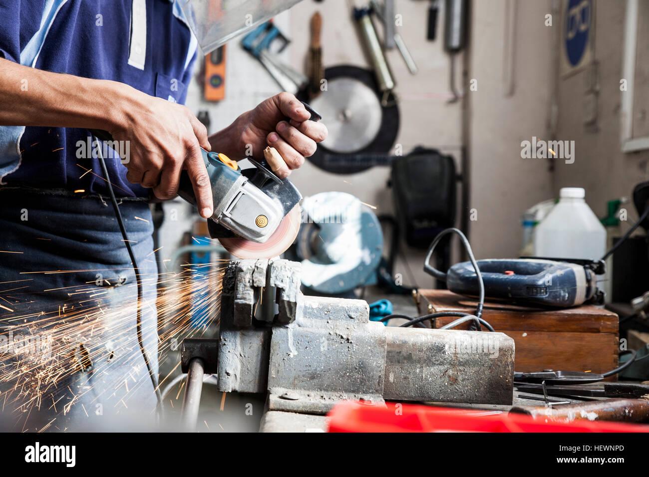 La sezione centrale del giovane uomo utilizzando smerigliatrice angolare in officina di riparazione Immagini Stock