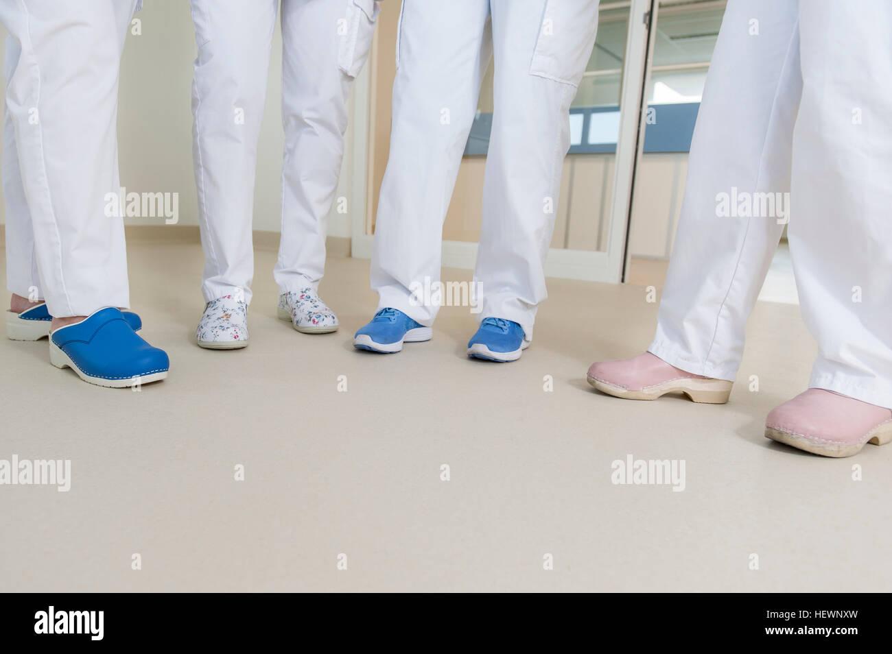 Sezione bassa del gruppo di infermieri indossando scrub chirurgico e zoccoli Immagini Stock
