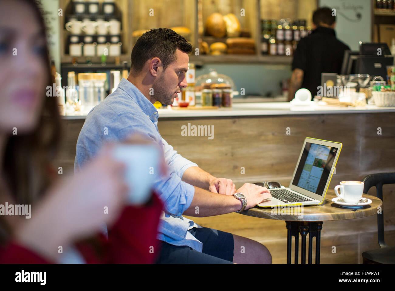 Uomo seduto in cafe portatile di lettura Immagini Stock