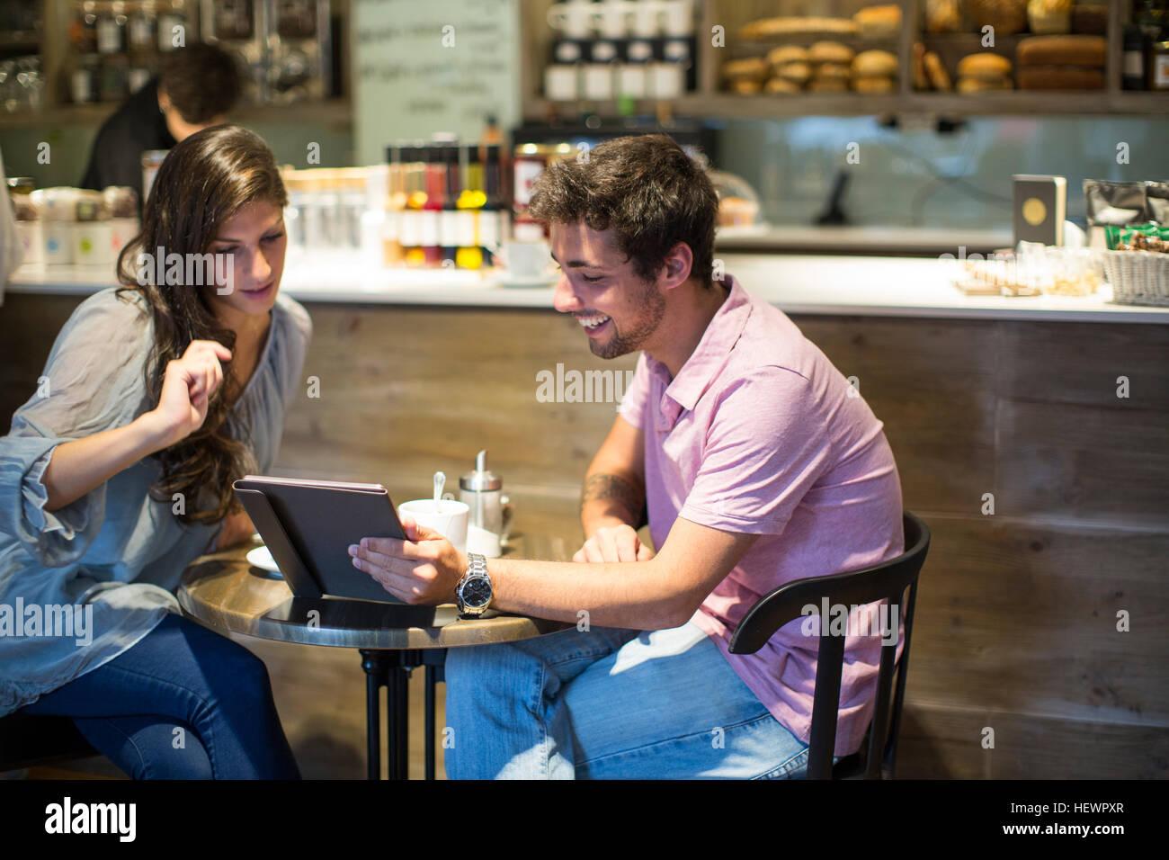 Coppia giovane in cafe guardando a tavoletta digitale Immagini Stock