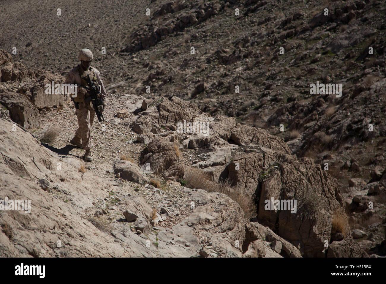 Stati Uniti Marine Corps Gunnery Sgt. Donnie ponti, la società gunnery sergente con Echo Company, 2° Battaglione, 7° Reggimento Marine, Regimental Combat Team 7, si arrampica su di una collina di condurre un sondaggio del sito nel quartiere Kajaki, provincia di Helmand, Afghanistan, Febbraio 8, 2013. (U.S. Marine Corps foto di Cpl. Kowshon Ye/RILASCIATO) 130208-M-QZ858-031 (8473166459) Foto Stock
