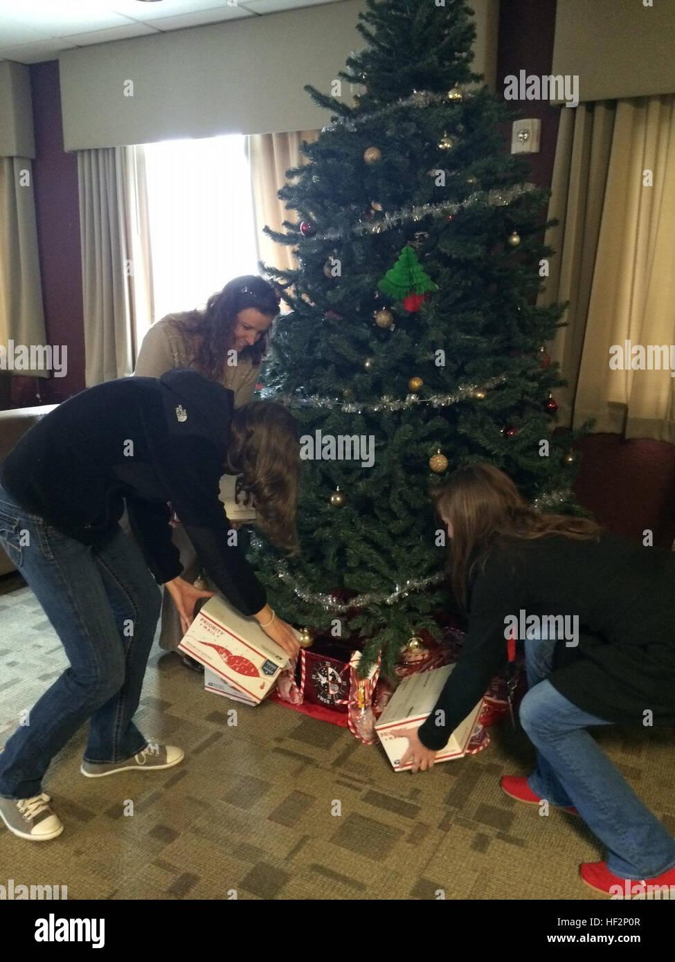 Icy Munchel, sinistra, Megan Goold, centro e Katie Contento hanno luogo i pacchetti di cura sotto un albero di Natale Immagini Stock