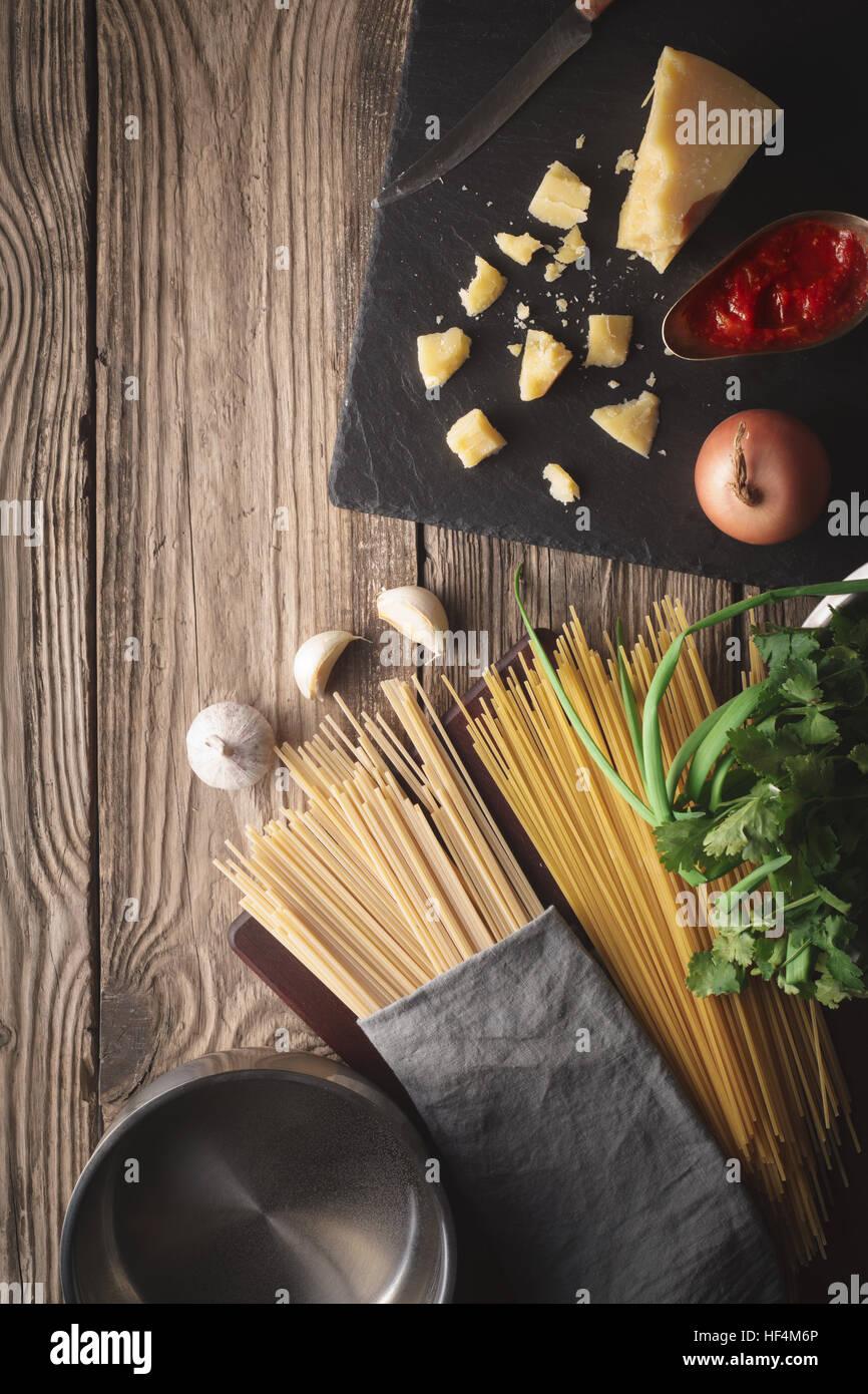 Gli ingredienti per cucinare gli spaghetti con formaggio ed erbe fresche sul vecchio tavolo in verticale Immagini Stock