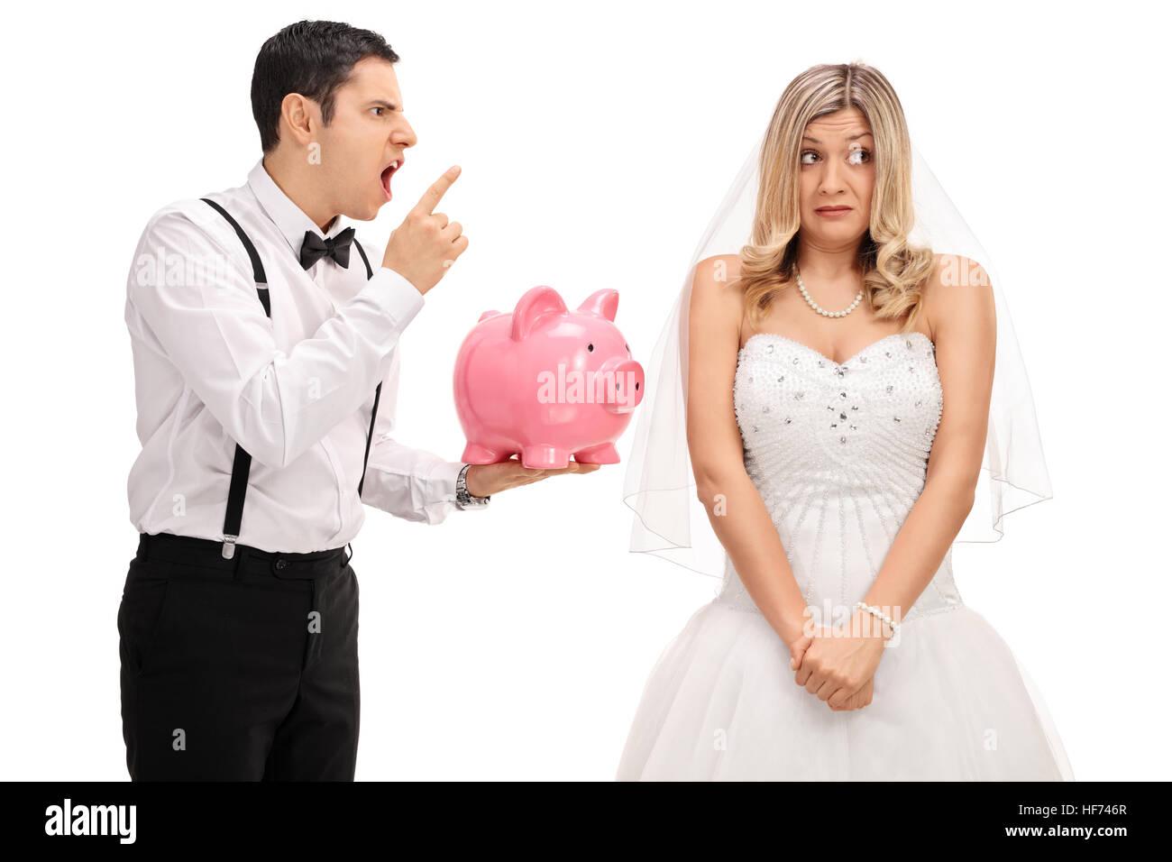 Arrabbiato groom tenendo un piggybank e scolding un imbarazzato sposa isolati su sfondo bianco Immagini Stock