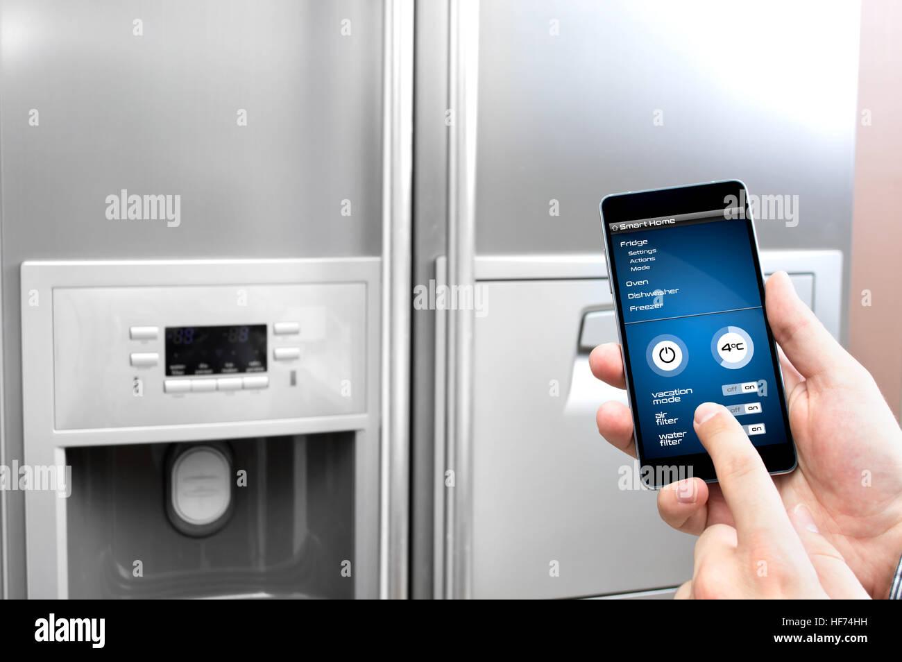 Uomo usa il suo smartphone per impostare il frigo Immagini Stock