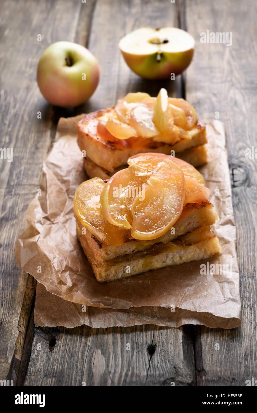 Mele caramellate su pane tostato su sfondo di legno Immagini Stock