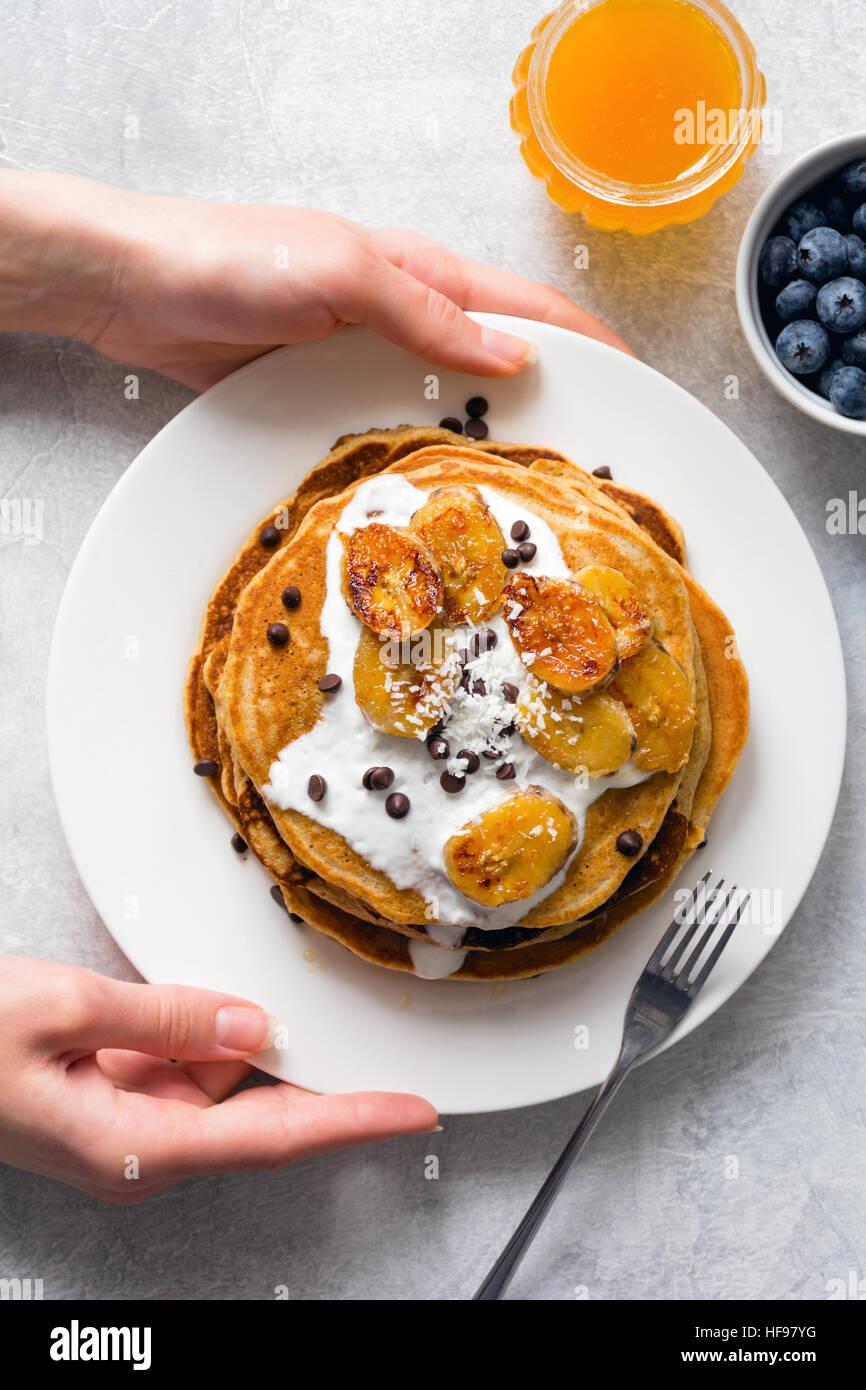 Pancake per colazione. Pancake caramellato con banana, lo yogurt e il cioccolato. Donna mani tenendo la piastra Immagini Stock
