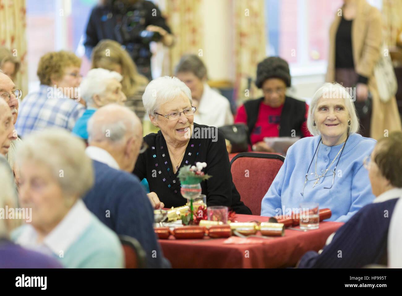 Il vecchio le persone godono di una festa di Natale alla chiesa della Santa Trinità Hall , Southport Immagini Stock